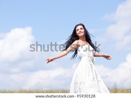 beautiful young brunette woman outdoor on the hill on a summer day, against blue sky with clouds