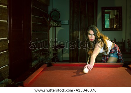 Beautiful young  brunette woman playing billiard on red table indoors. Toned image. Warm atmosphere. - stock photo