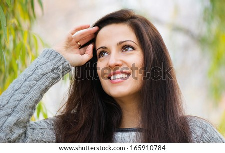 Beautiful young brunette woman portrait smiling outdoors - stock photo