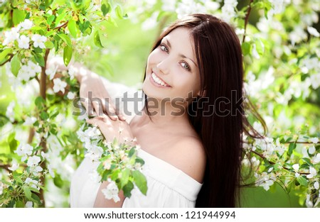 beautiful young brunette woman standing near the apple tree on a warm summer day - stock photo