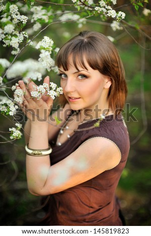 beautiful young brunette woman standing near tree