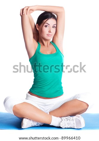 beautiful young brunette woman stretching the muscles of her arms, isolated against white background