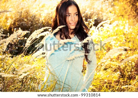beautiful young brunette woman walking through sunny yellow autumn field - stock photo