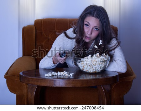 Beautiful young brunette woman watching TV in armchair. - stock photo