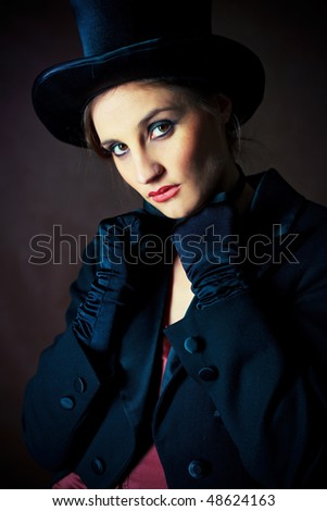 beautiful young brunette woman wearing a black cylinder hat, a smoking jacket and a butterfly bow tie