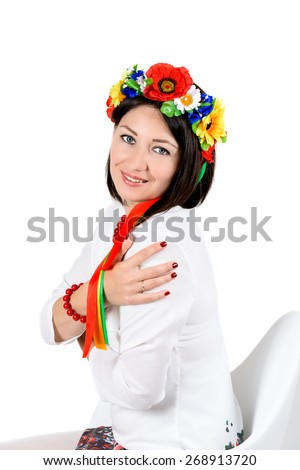 beautiful young brunette woman wearing national ukrainian clothes posing in studio on white background - stock photo