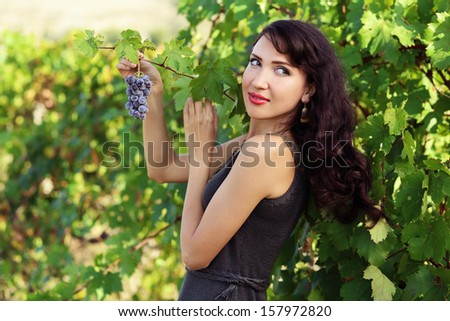 Beautiful young brunette woman with a bunch of grapes in vineyard - stock photo