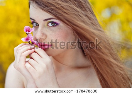 beautiful young brunette woman with a flower - stock photo