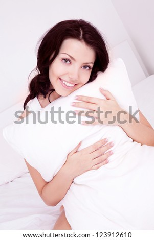 beautiful young brunette woman with a pillow in bed at home - stock photo