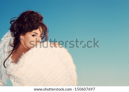 beautiful young brunette woman  with angel wings against blue sky,  outdoor shot, small amount of grain added