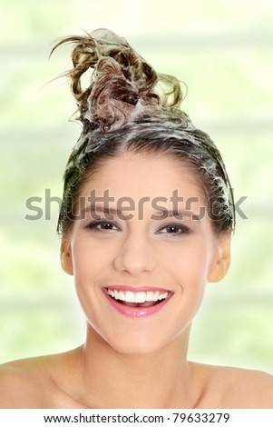 Beautiful young brunette woman with attractive smile soaping her head - stock photo