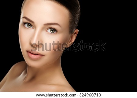 Beautiful young brunette woman with clean fresh skin with nude makeup with hands at face. Closeup real photo - stock photo