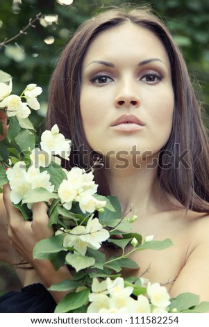 beautiful young brunette woman with jasmine looking into the camera