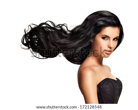 Beautiful   young brunette woman with long black curly  hair posing at studio