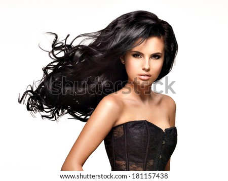 Beautiful   young brunette woman with long black curly  hair posing at studio - stock photo