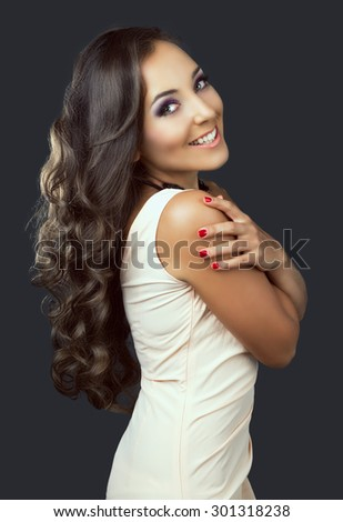 beautiful young brunette woman with long curly hair, against dark grey studio background - stock photo