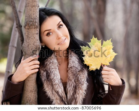 beautiful young brunette woman with maple leaves in her hands,  spending time in the autumn park - stock photo