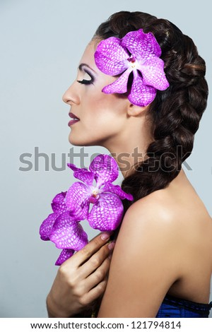 Beautiful young brunette woman with orchid . Wedding Hairstyle. Violet Bride.