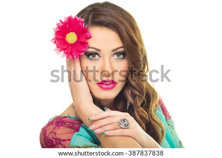 Beautiful young brunette woman with pink flower in her hair. Gorgeous green eyed Caucasian female model posing, wearing makeup. Retouched, isolated on white background. - stock photo