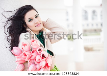 Beautiful young brunette woman with pink tulips - stock photo
