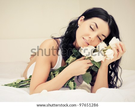 beautiful young brunette woman with roses in bed at home - stock photo