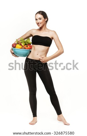 Beautiful young brunette woman with slim body holding bowl with fruits and vegetables. Healthy eating lifestyle and weight loss concept.  Isolated on white - stock photo
