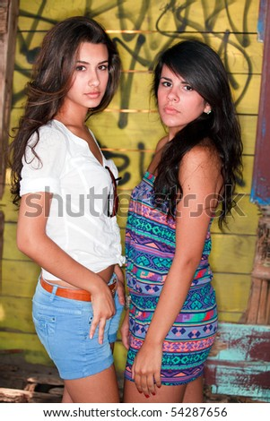 Beautiful Young Brunettes in a Fashion Pose with a graffiti background - stock photo