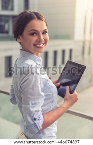 Beautiful young business lady is holding a tablet, looking at camera and smiling, standing on balcony outside the office building