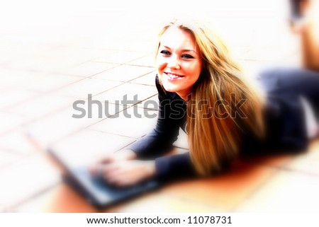 Beautiful young business student in the city typing on a laptop computer