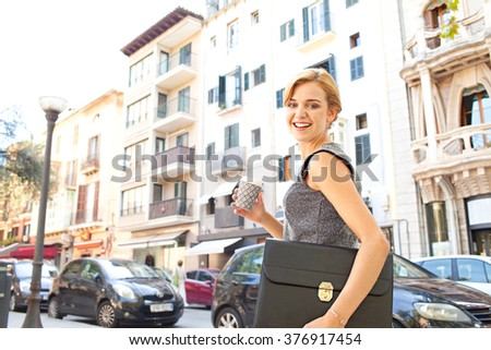 Beautiful young business woman commuter walking in classic office buildings city, holding a coffee paper cup and smiling and looking. Professional businesswoman drinking on the go lifestyle exterior. - stock photo