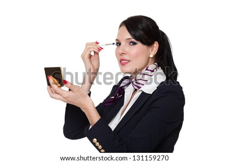 Beautiful young business woman dressed in a navy suit with a purple scarf and white shirt standing smiling and applying her eye makeup, isolated on white background - stock photo