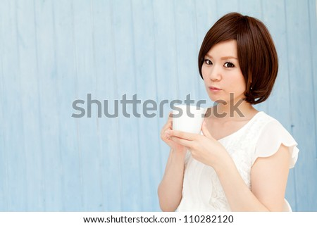 Beautiful young business woman drinking tea. Portrait of asian.