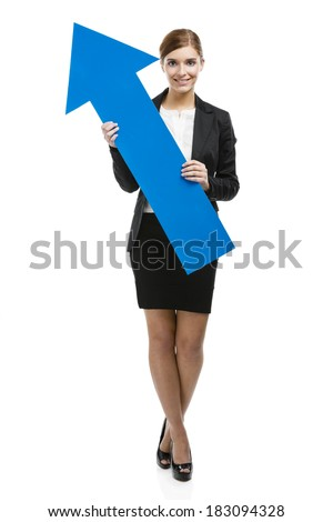 Beautiful young business woman holding a blue arrow, over a white background - stock photo