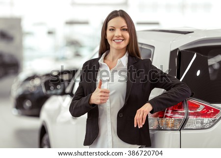 Beautiful young business woman in classic suit is smiling and looking at camera while leaning on a car in a motor show