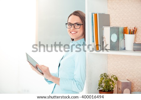 beautiful young business woman in modern office with big window and cupboard full of office supplies big beautiful modern office photo