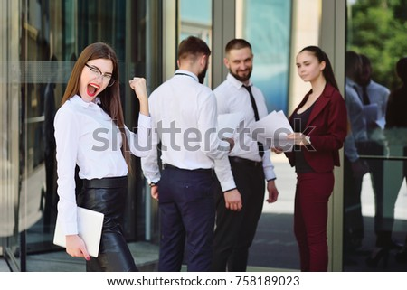 beautiful young business woman is happy against the background of an office building and colleagues or co-workers. Success in business. Career. long-awaited vacation