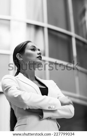 Beautiful young business woman. Modern building behind her - stock photo