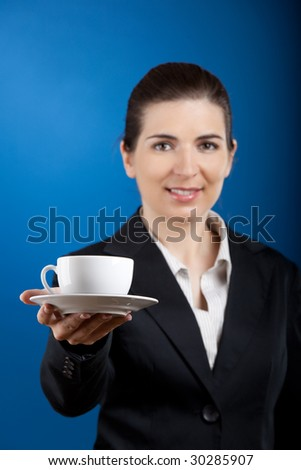 Beautiful young business woman offering a cup of tea - stock photo