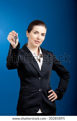 Beautiful young business woman olding keys - focus is on the model