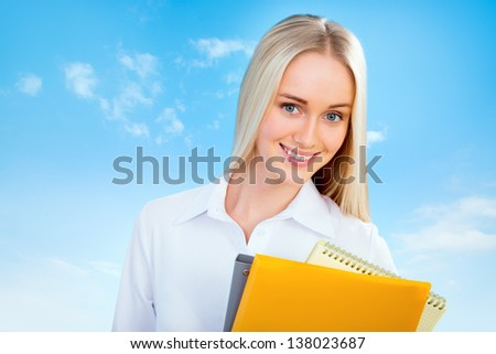 Beautiful young business woman on a blue sky background