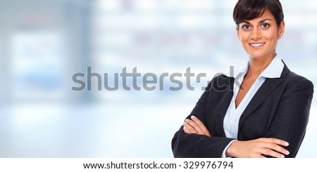 Beautiful young business woman over blue office background.