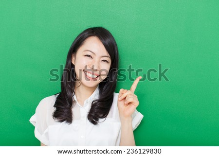 beautiful young business woman pointing copy space against green background  - stock photo