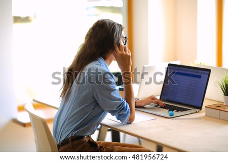 Beautiful young business woman sitting at office desk and talking on cell phone