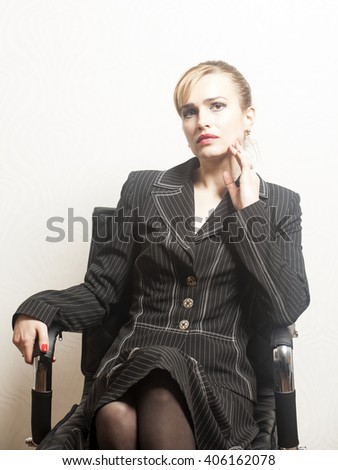 Beautiful young business woman sitting on a chair in office - stock photo