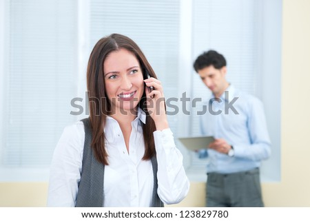 Beautiful young business woman speaks on a mobile phone. Young businessman with digital tablet on the background in soft focus.