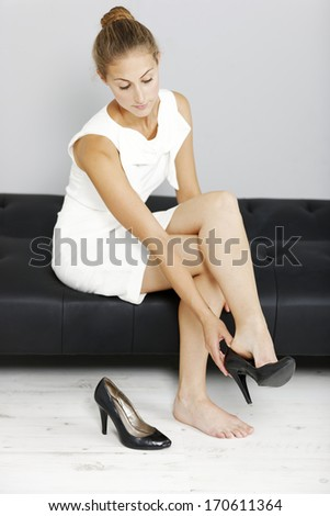 Beautiful young business woman taking her shoes off after a long day. - stock photo
