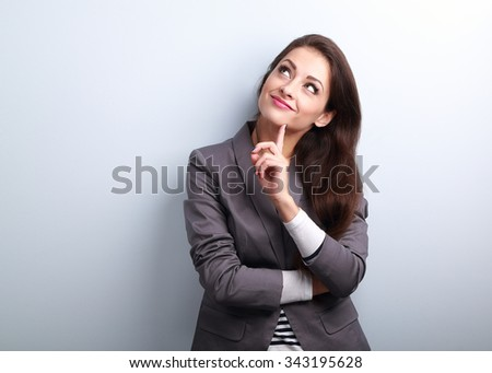 Beautiful young business woman thinking and looking up on blue background - stock photo