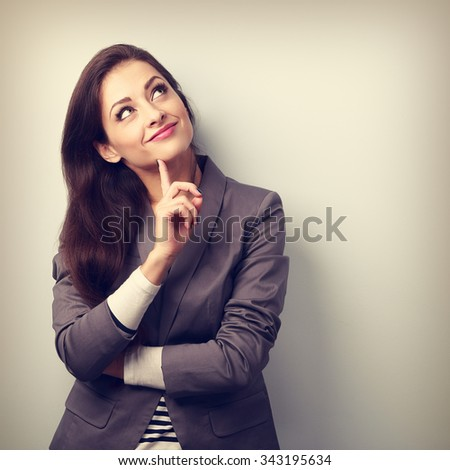 Beautiful young business woman thinking and looking up with finger under the face. Toned closeup portrait - stock photo