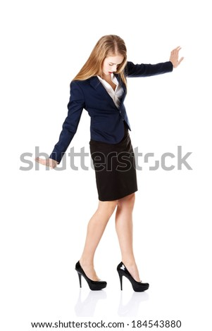 Beautiful young business woman trying to keep balance. Isolated on white. - stock photo