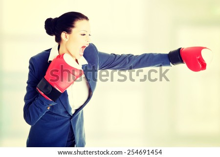 Beautiful young business woman wearing boxing gloves. - stock photo